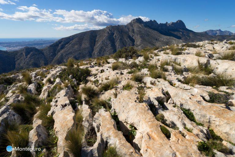 Lapiaz en la meseta de la Sierra de Oltà, Sierra de Bernia al fondo